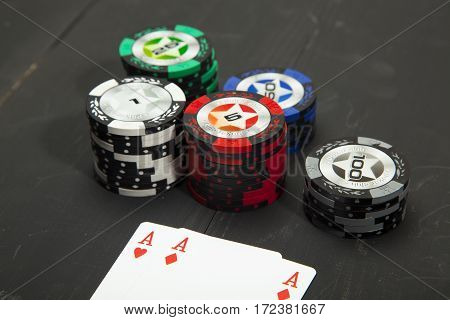 Chips and playing cards on a dusty wooden table with black background