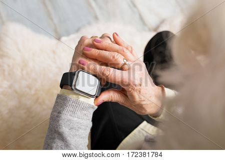 Old person using smart watch on her wrist