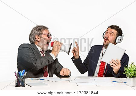 The two colleagues working together at office on white studio background. one man shouting through a megaphone - other in headphones can not hear nothing