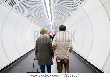 Beautiful senior couple walking in the hallway of subway in Vienna pulling a trolley luggage. Rear view.