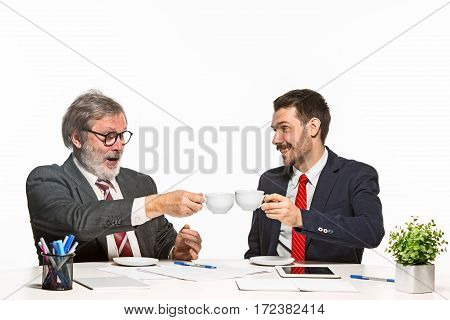 The two colleagues working together at office on white studio background. They actively and emotionally discussing current plans with cups of coffee