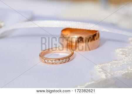 couple of gold wedding diamond ringson wedding pillow
