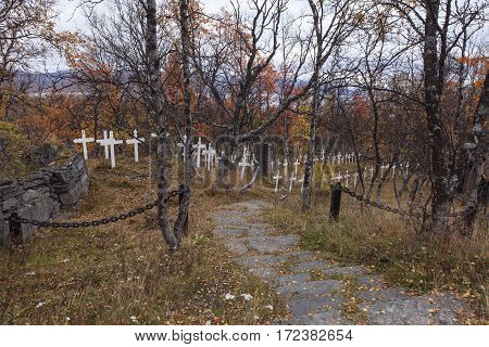 Colorful cemetery in autumn, fall. Gate, chains this side the white crosses.