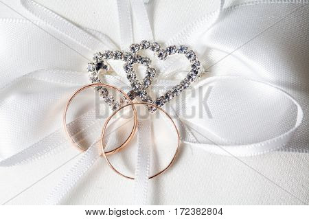 Two wedding rings on decorative pillow with heart shaped object