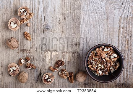 walnuts in a clay plate on a wooden background. top view