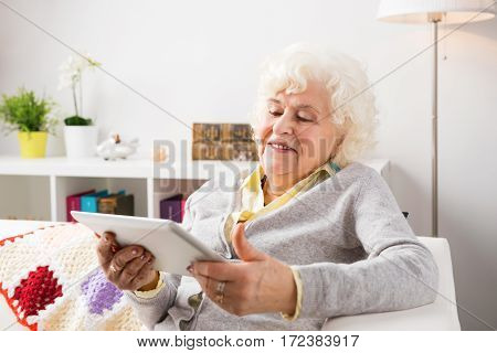 Grandmother using tablet computer in her living room