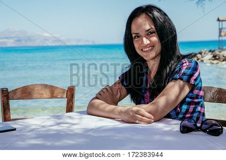 girl at the table in a cafe on the background of the sea Crete Greece