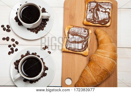 Cups Of Coffee With A Croissant And Toast With Chocolate On A White Wooden Table