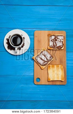 Cup Of Coffee And Toast With Chocolate On A Blue Wooden Table