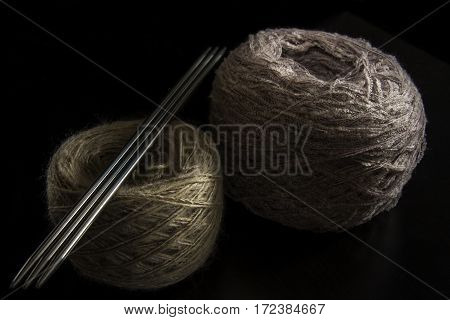 Two balls of wool and needles on a black background. yarn of isolated