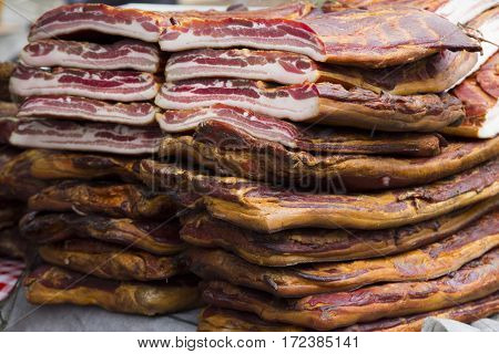 Home made smoked bacon in a street market selective focus and small depth of field