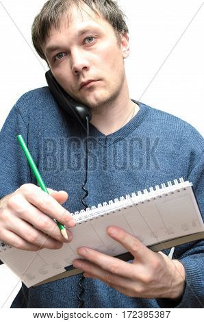 young man talking on the phone and making notes