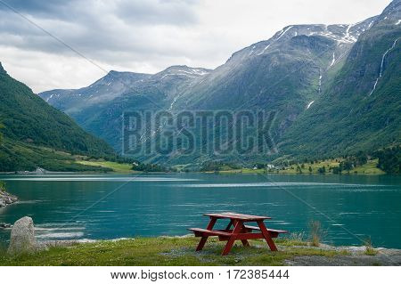 Wooden barbecue furniture on the shore of Oldevatnet fjord, Norway. Evening light landscape.