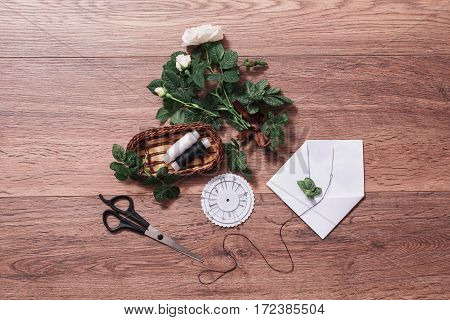 Threads pins needles scissors lying on wooden background. White envelope and a white rose. Greeting card. Conceptual photography. Wedding invitation card. Valentine day. Flat lay copyspace