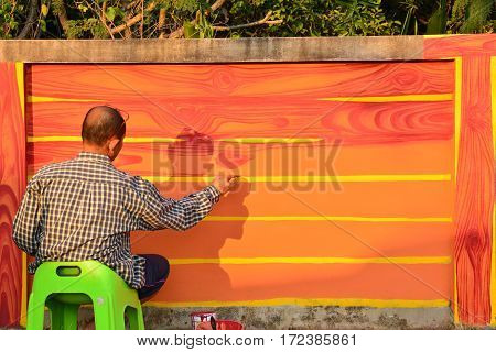 Paintbrush in hand of man and painting on the wall at morning