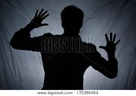 Shadow Of Man Behind Dark Fabric