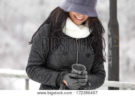 Smiley brunette female drinking coffee in winter nature