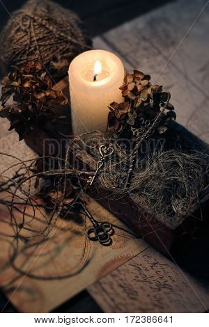 still life in retro style with a burning candle old keys dry flowers a ball of thread.
