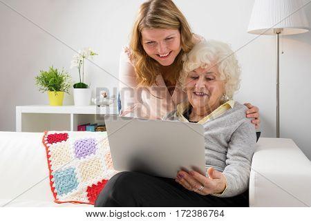 Grandaughter teaching grandma how to use modern computer
