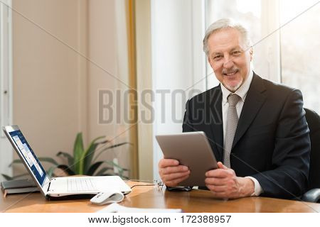 Businessman holding a tablet while sitting in his office