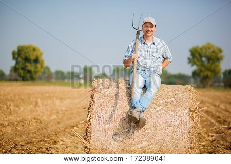Farmer sitting on a hay bale
