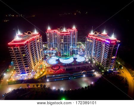 ALANYA, TURKEY - AUG 16, 2015: Three buildings of apartment complex Azura Park Residence with red light at night, aerial photo