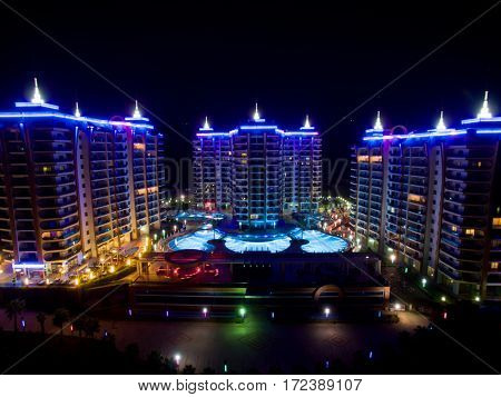 ALANYA, TURKEY - AUG 16, 2015: Three buildings of housing complex Azura Park Residence with color light at night, aerial photo