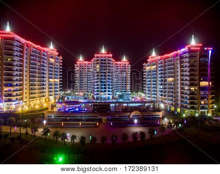 ALANYA, TURKEY - AUG 16, 2015: Three buildings of the residential complex Azura Park Residence with color light at night, aerial photo