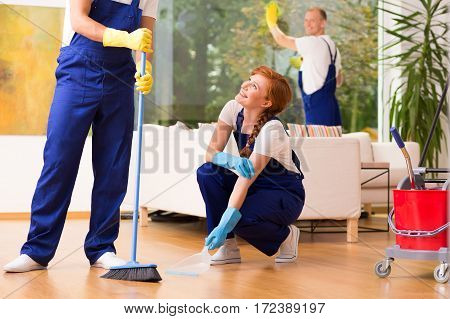 Co-workers with broom during professional house cleaning