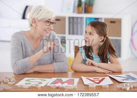 Child Studying Alphabet With Teacher