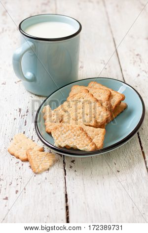 crackers on a blue plate and a mug of milk on a white wooden background