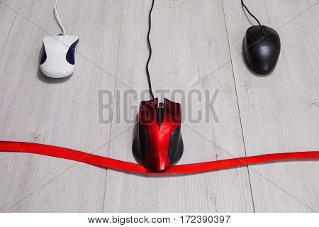 Interactive race on speed between red white and black computer mouse on wooden background. Input device for cursor control. Red ribbon. Competition in the business red tape.