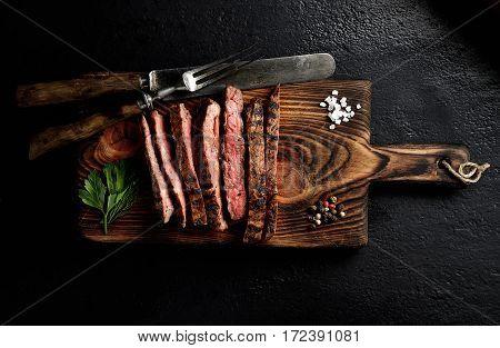 grilled beef on a board on a black background, knife, fork and salt