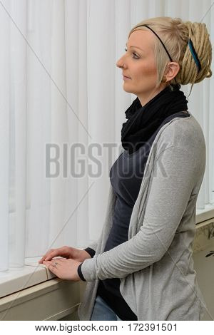 Young woman stands thoughtfully in front of the window - copy-space