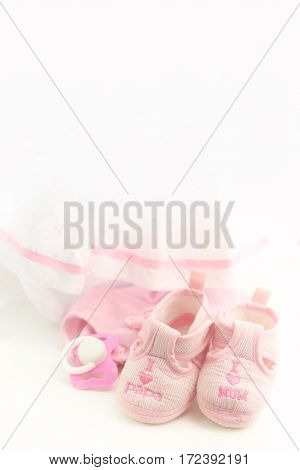 Pink baby booties on a bright pink background. Baby Clothing.