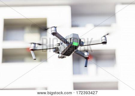 Black Drone Quadcopter Flies Between White Buildings