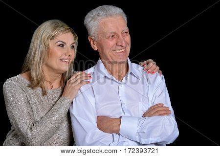 mature couple portrait posing against black background