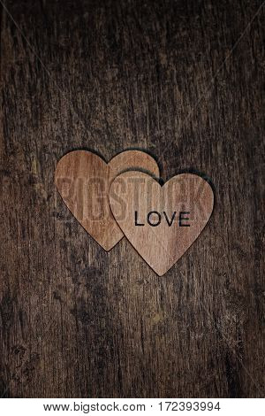 Two wooden hearts with word love on wood textured background.