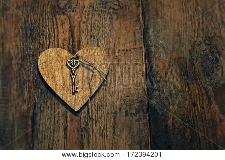 Wooden heart with a key on wood textured background.
