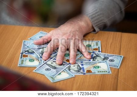 male hand and a hundred dollar bill. Greedy rich man. Cash proceeds