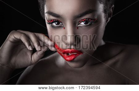Close-up of a beautiful black woman with fashion make-up red lips. Glamorous portrait