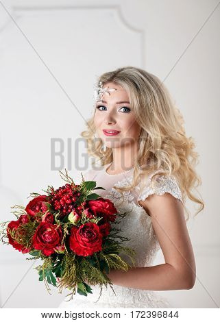 Portrait of beautiful bride with bouquet, gorgeous blonde bride with curly hairstyle in vintage white lace wedding dress holding red peonies bouquet, sensual look, fairytale woman.