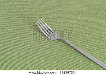 One fork on a green sheet with copy space