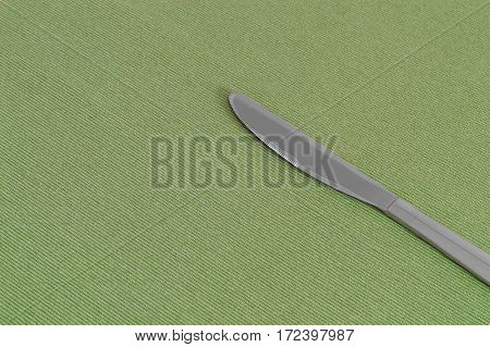One knife on a green sheet with copy space