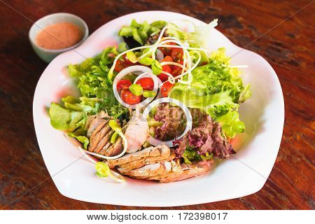 roasted pork salad with vegatables on white dish