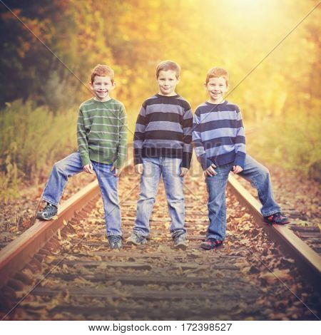 Three brothers standing an old rail tracks instagram filter