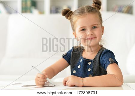 Portrait of a cute little girl drawing and smiling
