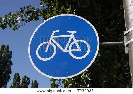 Blue sign indicating a bicycle track in Munich with a tree in the background