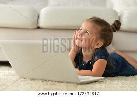 Portrait of a cute little girl using laptop
