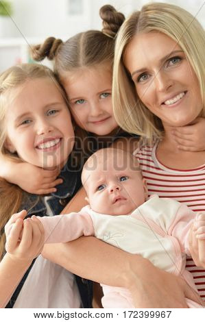 portrait of young happy mother with little daughters